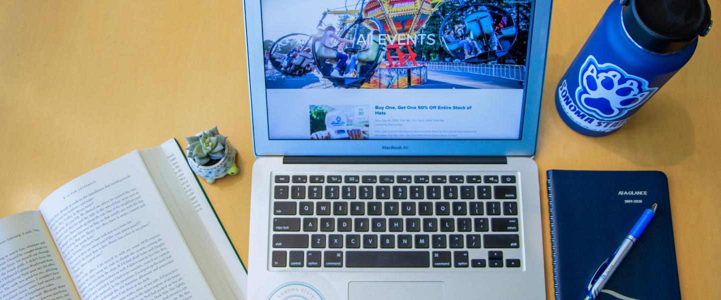 Computer with Seawolf Living website up, water bottle and planner and book